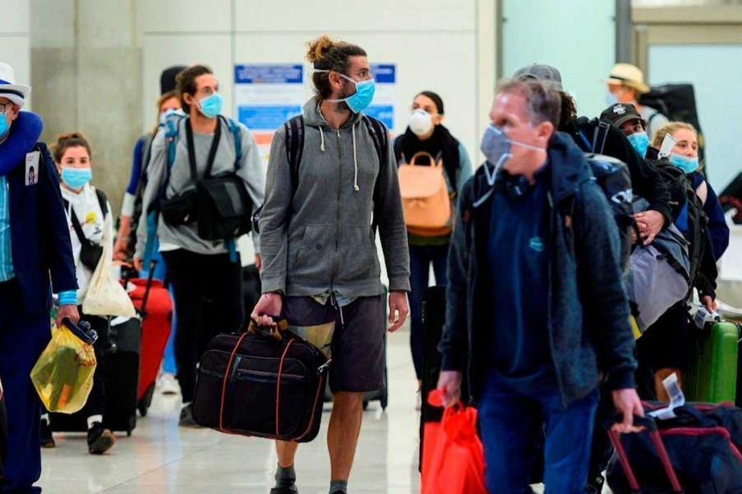 Personas en un aeropuerto con mascarillas